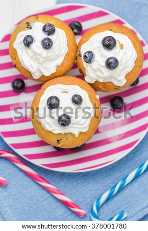 Sweet delicious muffins with cream and cranberries