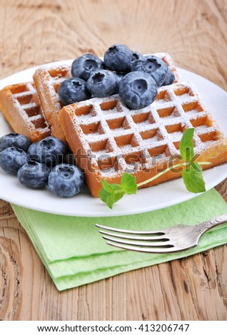 Sweet dessert: belgian waffles with blueberries sprinkled with powdered sugar.