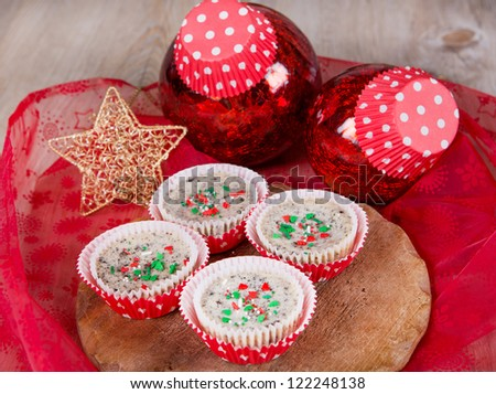 Sweet dessert - mini cheesecakes in muffin forms with red Christmas tree balls - stock photo