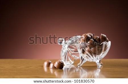 Sweet desserts, closeup shot of chocolate bonbons in elegant glass bowl. - stock photo