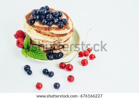 Sweet dietic pancake with blueberries raspberries and currents on white background. Top view
