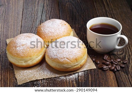 Sweet donuts with coffee cup for breakfast on rustic wooden table - stock photo