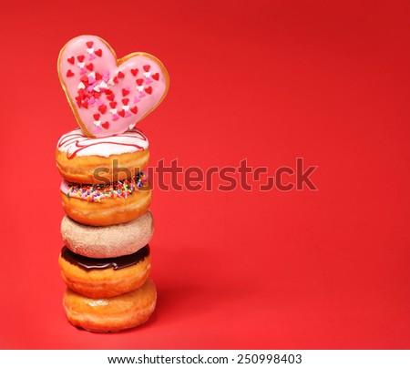 Sweet donuts with heart shaped donut on the top over red background