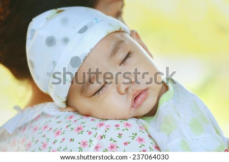 sweet dreams, Asian babe sleeping on his mother's shoulder, solf focus - stock photo