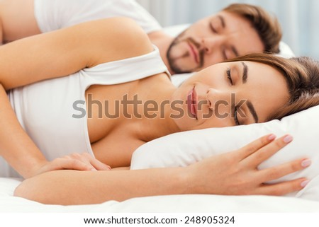 Sweet dreams. Beautiful young loving couple sleeping together in bed  - stock photo