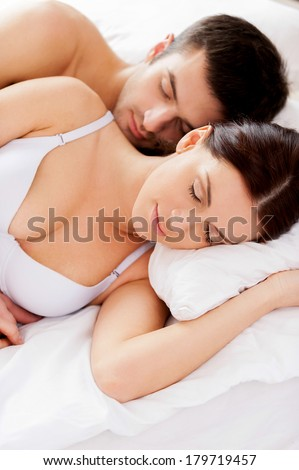Sweet dreams. Top view of beautiful young loving couple sleeping together in bed