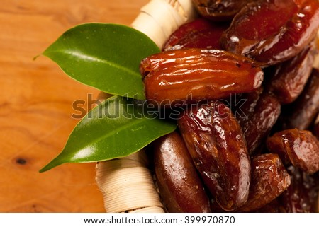 Sweet dried dates fruit in small bowl, mediterranean desert on wooden surface. - stock photo