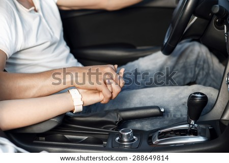 Sweet drive. Close up photo of a man driving a car holding a steering wheel with one hand and a hand of his lovely girlfriend in another