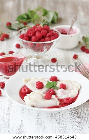 sweet dumplings, called varenyky or pierogi, with raspberries and berry sauce on a light background