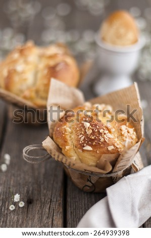 Sweet, Easter bread with yellow egg on old wood table - stock photo