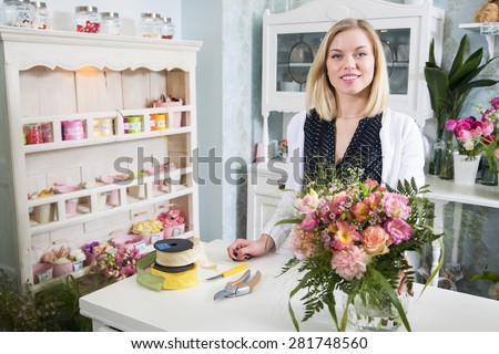 Sweet female florist welcomes her new customer - stock photo