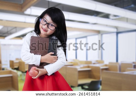 Sweet female little student smiling at the camera while holding a book and apple in the class - stock photo