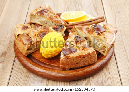 sweet food : cuts of apple pie on wooden plate with cinnamon sticks and lemons