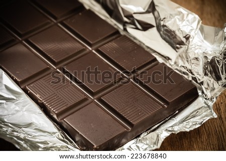 Sweet food. Dark chocolate bar in opened silver foil wrapping on wooden table. - stock photo