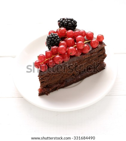 Sweet food. Delicious chocolate cake with berries on top - stock photo
