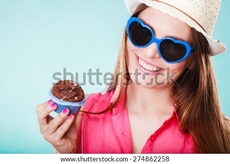 sweet food happiness and people concept. Smiling summer fashionable woman wearing straw hat heart shaped sunglasses holds cake cupcake in hand blue background - stock photo