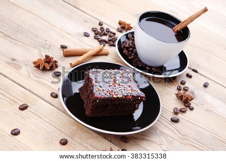 sweet food : hot black fragrant coffee and chocolate cake with cinnamon sticks, coffee beans, and anise star - stock photo