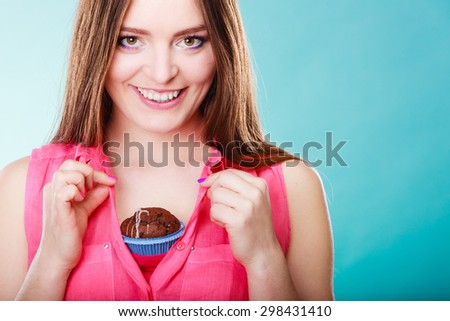 sweet food or sex for brighten moods. Smiling woman having fun holds chocolate muffin cake on her chest blue background - stock photo
