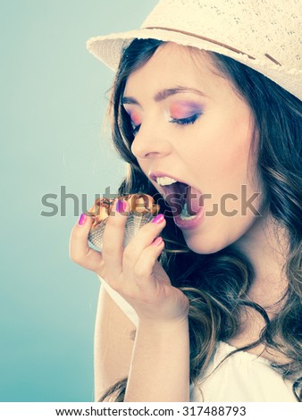 Sweet food sugar make us happy. Attractive woman summer clothing holds cake in hand eating filtered photo