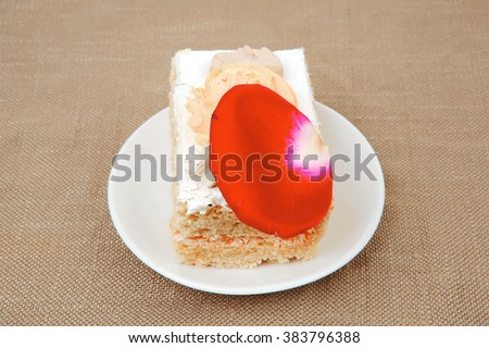 sweet food: tender cheese cream cake served on white dish with roses - stock photo