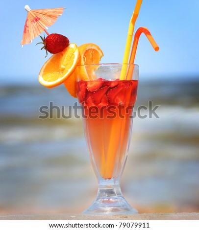 sweet fruit cocktail on beach - stock photo