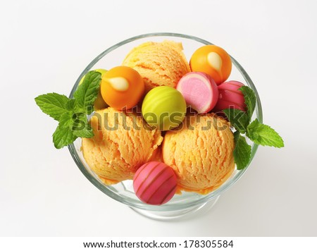 Sweet fruit pralines with scoops of assorted ice cream  in a glass cup - stock photo