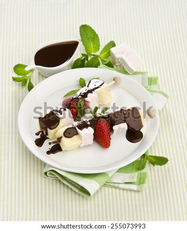 sweet fruit skewers with banana strawberry marshmallow drizzled with chocolate sauce and mint on a white plate
