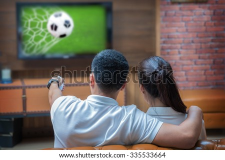 Sweet fsmily with Football match and remote control - stock photo