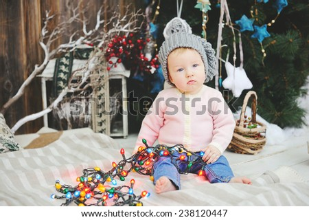 Sweet funny baby girl playing with Christmas tree decoration