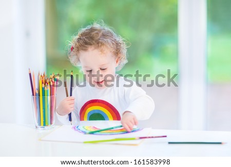 Sweet funny toddler girl painting a rainbow in a white room with a big window into the garden - stock photo