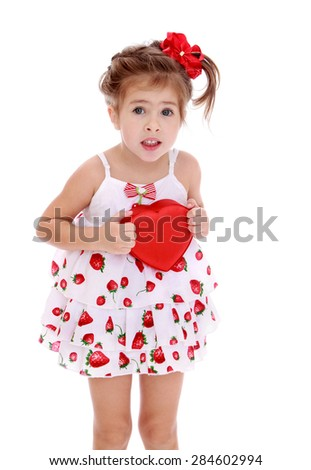 Sweet gentle little girl holds up a box in the shape of a heart- isolated on white background