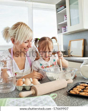 Sweet girl baking cookies with her mother - stock photo