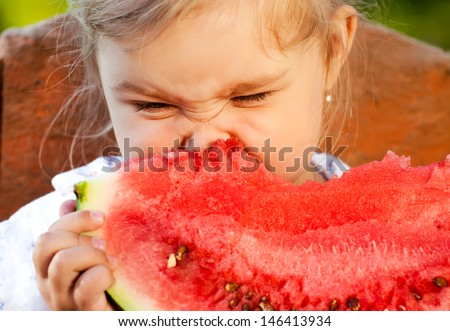 Sweet girl eating watermelon on a summer morning