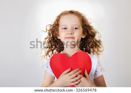 Sweet girl holding red paper heart. Valentines day or healthcare, medical concept. - stock photo