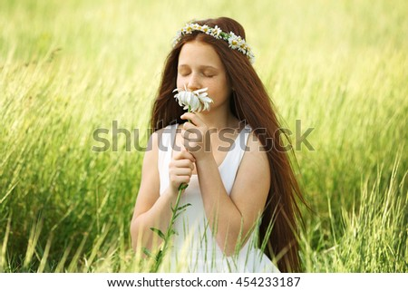 Sweet girl in meadow with chamomile flowers