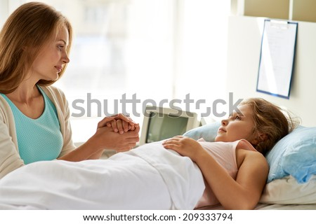 Sweet girl lying in bed in hospital with her mother near by - stock photo