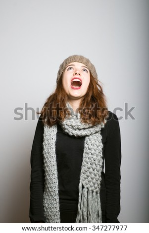 Sweet girl screaming angry, winter Christmas and New Year concept isolated studio shot on a gray background