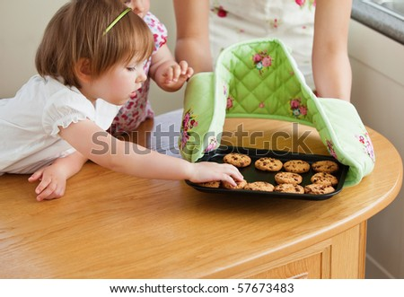 Sweet girl taking a small cookie in the kitchen - stock photo