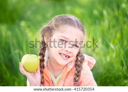 Sweet girl with a fallen toth holding an apple in her hand on nature - stock photo