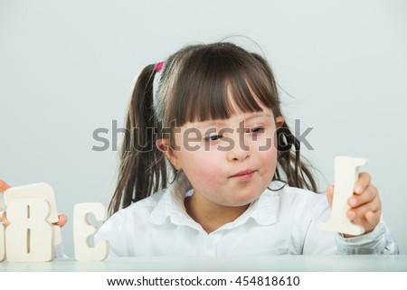 Sweet girl with Down Syndrome, playing with wooden numbers
