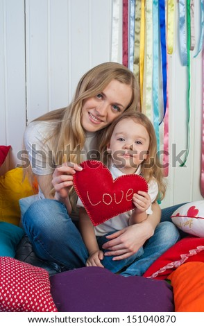Sweet girl with mother with red heart in studio