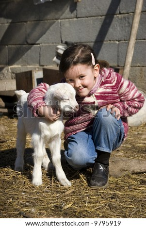 Sweet girl with new born goat in th e farm - stock photo
