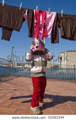 sweet girl with pink digital camera and clothesline - stock photo
