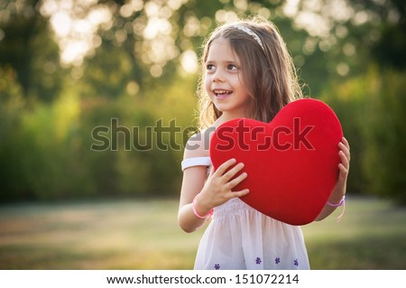 Sweet girl with red heart outdoors in the park.  - stock photo