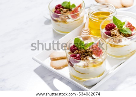 sweet greek yogurt with honey and fresh figs on white table, horizontal