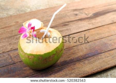 Sweet green coconuts water with drinking straw on wooden board. Coconut tropical fruit in Koh Samui, PhaNgan and koh tao , surat thani and chumphon at Thailand. selective focus. soft and blur focus