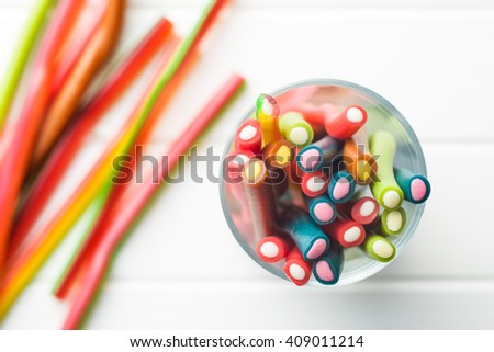 Sweet gummy sticks with different flavor. Top view of tasty candy in glass cup. - stock photo