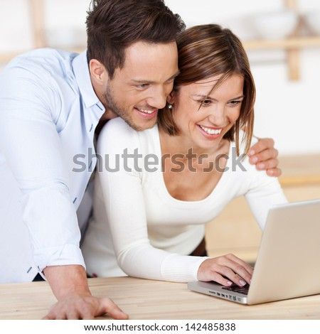 Sweet happy couple browsing the internet at the laptop - stock photo
