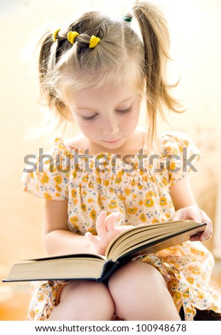 sweet happy little girl reading a book