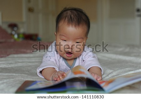 sweet happy little girl reading book